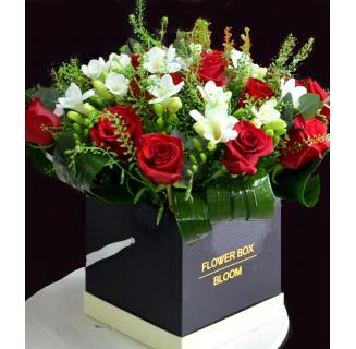 Cutie cu trandafiri roșii și frezii